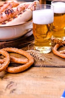 木製の泡と新鮮なビール。オクトーバーフェストドイツのプレッツェル。