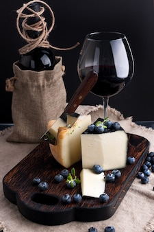 ペコリーノチーズとブルーベリー、木の板、グラスとワインのボトル。
