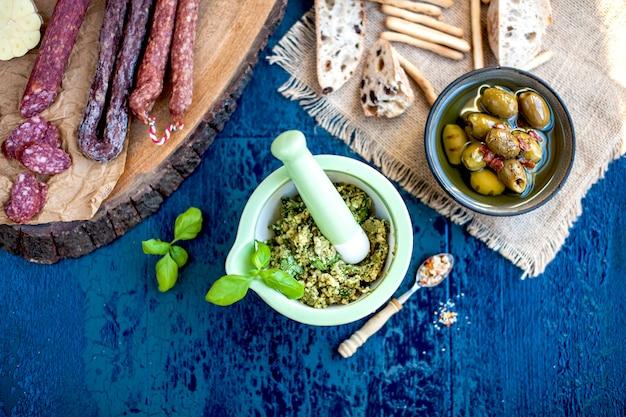 グリーンカップのペストソース、オリーブ、木の板に盛り合わせたサラミ、オリーブと青の表面、スライスしたパン