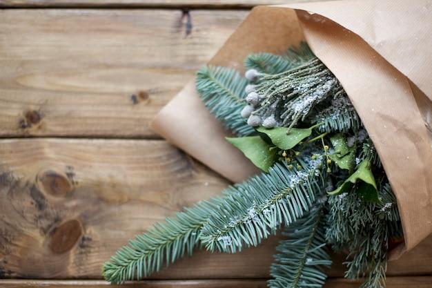Еловые ветки в оберточной бумаге, на деревянном