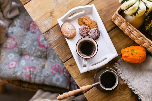 秋と冬の家の静物画。上からの眺め。家庭的な雰囲気とインテリアのコンセプト。シナモンと木製のテーブルビスケットクッキー。