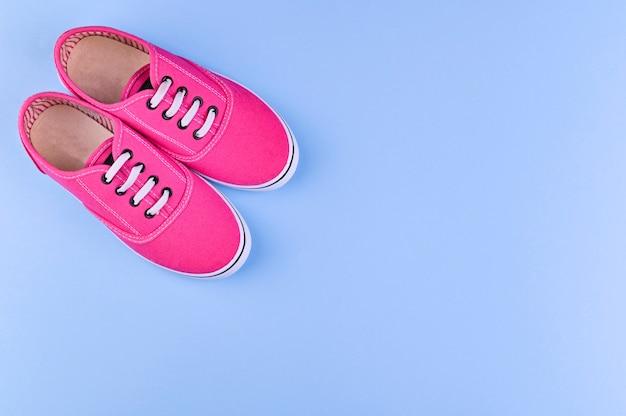青色の背景に女の子のためのピンクのスニーカー。テキスト用の空きスペース。子供服の販売。上面図