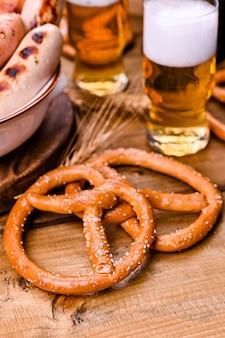新鮮なクラフトビール。ビール祭りのための伝統的なドイツのソーセージとペストリーのブレーゼル