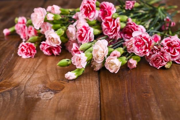 木製のテーブルにピンクと白の花びらとカーネーション