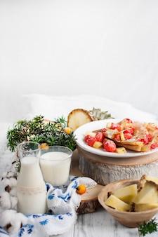 Домашние блины с клубникой и ананасом на белой тарелке с молоком