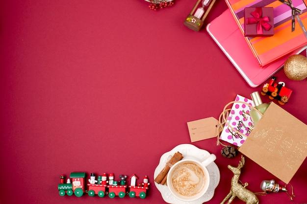 Новогоднее украшение и подарок. утренний ароматный кофе и лепестки роз. вид сверху. разные предметы и елочные игрушки на красном фоне.