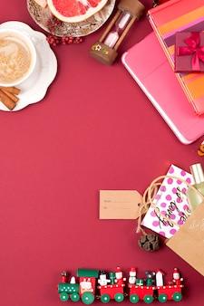 Новогоднее украшение и подарок. утренний ароматный кофе и лепестки роз. вид сверху. разные предметы на красном фоне. копирование пространства, плоская планировка,