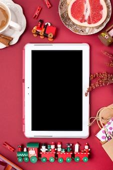 クリスマスの装飾とギフト。朝の香り高いコーヒーとバラの花びら。上面図。赤い背景のさまざまな主題。コピースペース、フラットレイ、