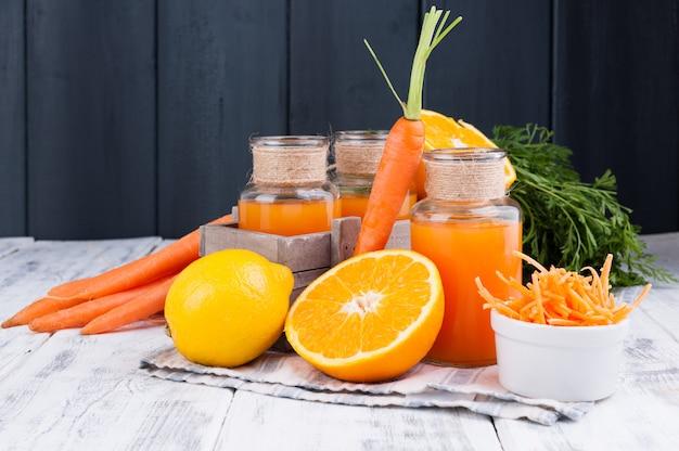 ニンジン、オレンジ、レモンのフレッシュジュース。葉と木の背景に他の新鮮な果物とニンジン。