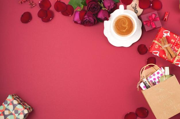 Чашка ароматного кофе и рождественские украшения на красном фоне. розы, подарки и рождественские сюрпризы. вид сверху. рамка. скопировать пространство