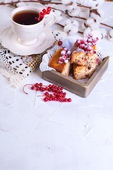 一杯の紅茶とソーサー、木の板と白い背景、綿の花に赤スグリのカップケーキ