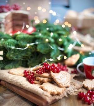 ベリーとビスケット、ギフト、村のテーブルの上のクリスマスツリーの近くのケーキ
