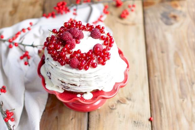 Белый торт с красными ягодами и веткой на деревянном столе