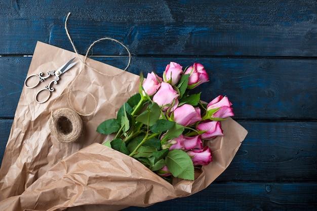 茶色の紙にピンクのバラの花束。カラーペストリーマカロニ