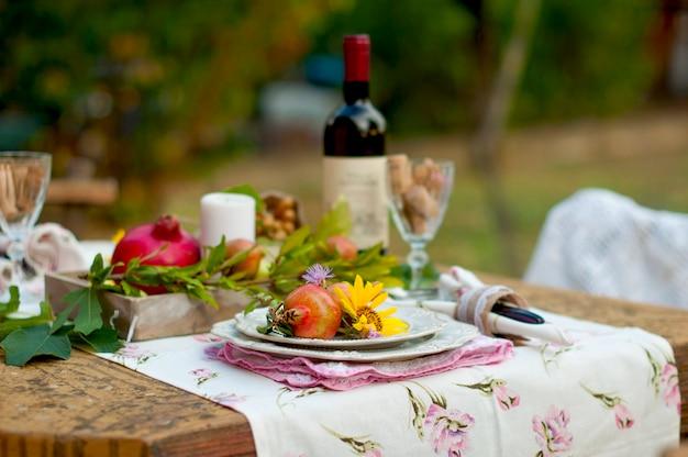 秋の庭、休日の雰囲気、居心地のよさで昼食はロマンチックです。ワインとフルーツを添えた屋外での秋のディナー。花とザクロの装飾テーブル。ビンテージ写真。