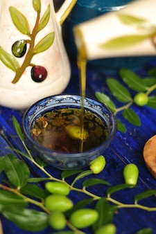 カップのオリーブオイル。新鮮なオリーブとオリーブの木の枝。グリーンオリーブ。庭で。木の板に。オイルの水差し。イタリアの古典。イタリアのオリーブ。イタリアの食べ物