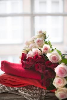 Много цветов роз, разная теплая одежда у окна. свитера на осень и зиму. чай и кот. свободное место для текста.