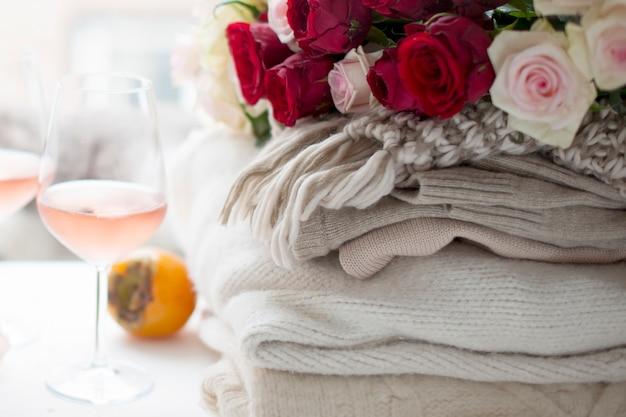 Два бокала вина и много зимней теплой одежды дома возле окна. кошка, большой букет роз и осенних фруктов в рамке. город за окном. свободное место для текста.