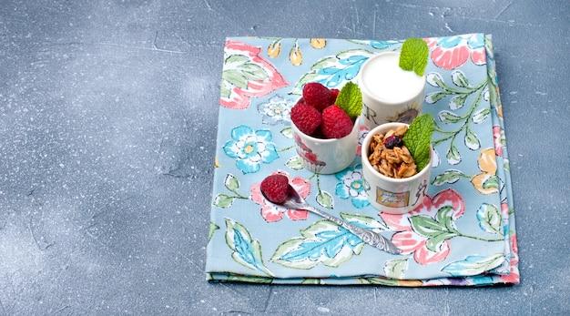 ヨーグルト、ミューズリー、灰色の背景と白いプレート上の果実とガラス