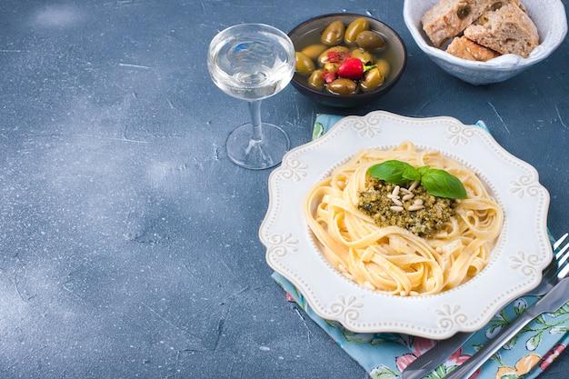 Тарелка с пастой с соусом песто и оливками на фоне камня