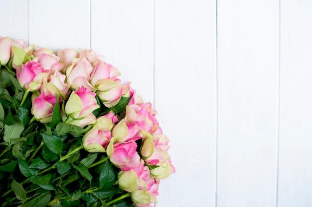 Большой букет роз с розовыми лепестками и зеленью на белом деревянном фоне