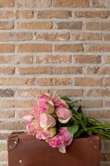 レンガの壁の近くの茶色のスーツケースにピンクのバラの花束