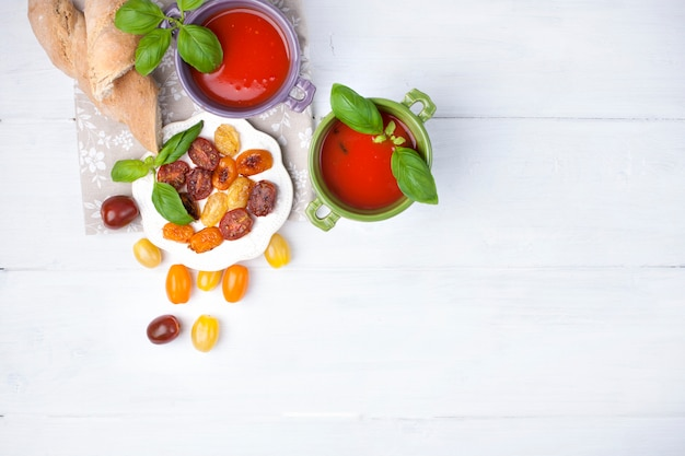 Суп госпачо в ярких чашках с базиликом на белом фоне