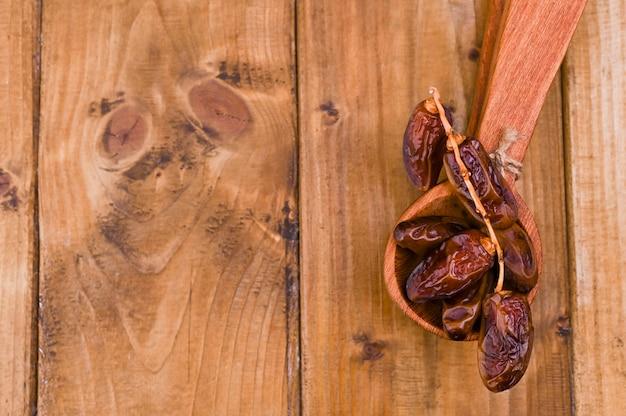 木製のテーブルにジューシーな日付。健康的な食事のためのドライフルーツ。コピースペース