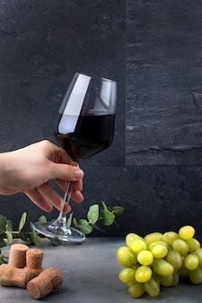 黒の背景に女性の手でワインのグラス。ブドウのピンクと緑