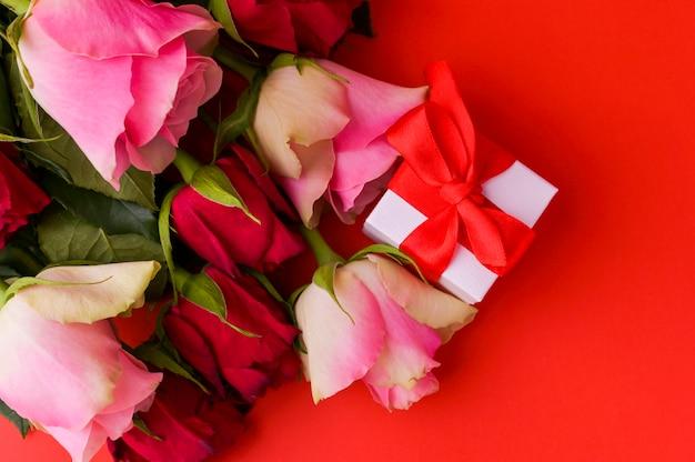 女性の日の概念とバレンタインのグリーティングカード。ギフト、バラと組成。テキスト用のスペース。