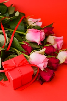 女性の日の概念とバレンタインのグリーティングカード。ギフト、バラ、封筒のコンポジション。テキスト用のスペース。