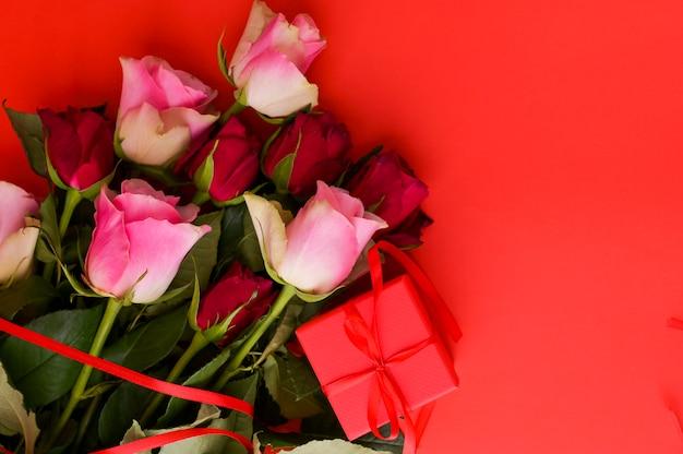 Женская концепция дня и поздравительная открытка дня святого валентина. композиция с подарком, розы. пространство для текста.