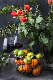 Клубника и ежевика в зеленой тарелке и мандарины в корзине возле вазы с букетом роз, на черном фоне. два бокала красного вина
