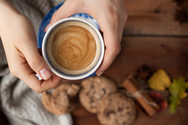 Утренний ароматный кофе в женской руке и на деревянном фоне. бисквитное печенье с шоколадом на завтрак и теплый вязаный плед. осеннее украшение. вид сверху. копировать пространство