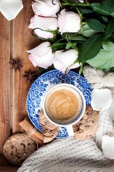 Романтический кофе в чашке на деревянном фоне с пледом, букетом белых роз и осенним уютом. доброе утро. вид сверху. скопировать пространство