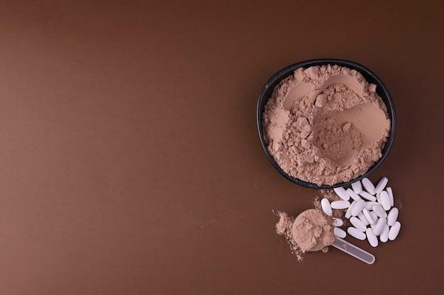 スポーツ栄養とバイオ食品サプリメントのコンセプト。薬と黒の背景に粉末のタンパク質。コピースペース。