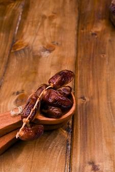 木製のテーブルでジューシーな日付。健康的な食事のためのドライフルーツ。コピースペース