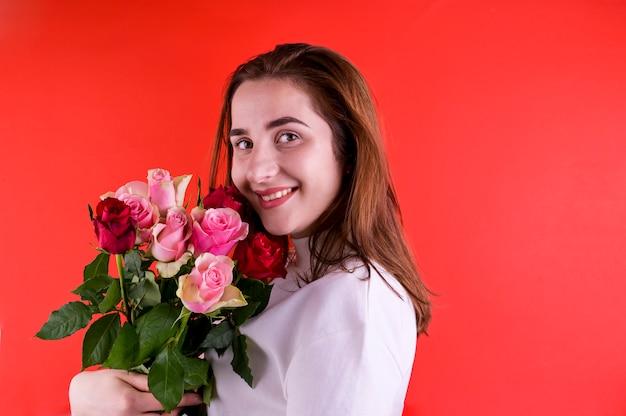 バレンタインデーと女性の日のコンセプトです。バラの花束を持って幸せな若い女の子