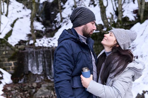 若い女性と男性が雪に覆われた森に寄り添います。冬服の恋人たちのペア。女の子は手に魔法瓶を持っています。コピースペース