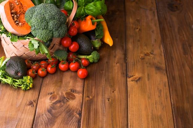 収穫。食品や健康的な食事のコンセプトです。さまざまな新鮮な野菜が入った大きなバスケット。コピースペース。セレクティブフォーカス