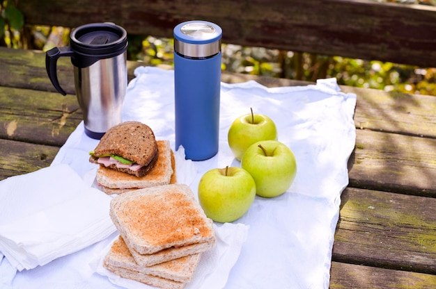 Бутерброды и два термоса с чаем и кофе на деревянном столе в парке на фоне зеленых листьев, дерева и солнечного света. концепция туризма и путешествий. копировать пространство