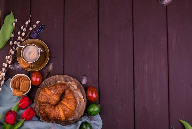 新鮮な芳香族エスプレッソとブラウニー、木製のテーブル。春の朝食、花、チューリップ、ペストリー、コーヒー。上面図。テキスト用の空き容量
