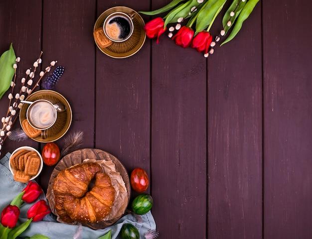 香り豊かな新鮮なエスプレッソ、クロワッサン、着色された卵、赤いチューリップ、柳のイースター朝食。コーヒー、ペストリー、木製のテーブルの上に花。上からの眺め。コピースペース