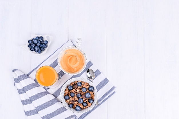 白い木製の背景に伝統的なヨーロッパの朝食。ミューズリー、ベリー、コーヒー、オレンジジュース。平干し。コピースペース