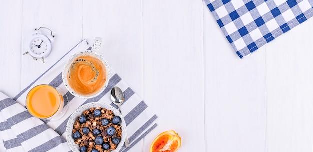 カップにブルーベリー、オレンジジュース、香り豊かなモーニングコーヒーを入れたミューズリー。白い木製の背景と目覚まし時計で朝食します。平干し。コピースペース