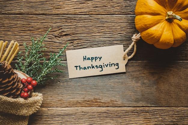 幸せな感謝祭の日の背景にカボチャ、木製テーブルにタグを挨拶