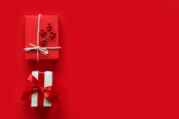 クリスマスプレゼントは赤の背景に提示します。シンプルでクラシックな赤と白のギフトボックスにリボン弓とホリデーホリデーデコレーション