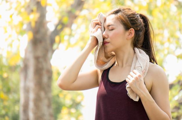 アジアスポーツの女性が公園で運動用のタオルを