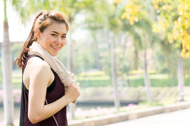 Азиатская женщина спорта с полотенцем бегом и работает в парке в центре города