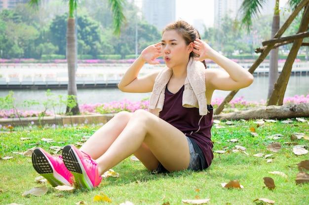 アジアのスポーツ女性が公園で座る
